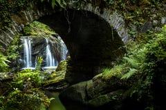 Ein Wasserfall unter der Brücke lizenzfreie stockfotografie