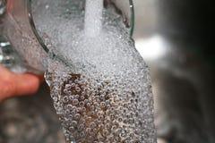 Ein Wasserstrahl füllt das Glas stockfotos