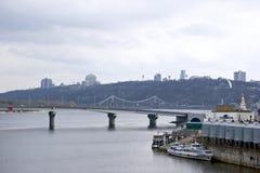 Ein Weg an einem bewölkten Tag entlang dem Damm und den industriellen Orten der Stadt entlang dem Fluss stockbild