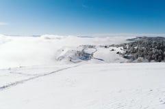 Ein Weg zu einem kleinen Dorf durch die schneebedeckte Steigung an der Spitze des Berges lizenzfreies stockfoto