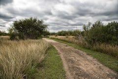 Ein Wegschotterweg mit stürmischem Himmel lizenzfreies stockbild