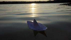 Ein Weißbuchboot schwimmt in ein Seewasser bei Sonnenuntergang in SlomO stock video