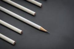 Ein weißer Bleistift unter vielen Bleistiften auf Schwarzem Stockfotos