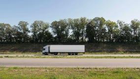 Ein weißer LKW bewegt sich entlang die Landstraße stock video