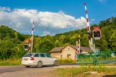 Ein weißer Personenkraftwagen, der einen Bahnübergang mit Sperren kreuzt stockfotografie