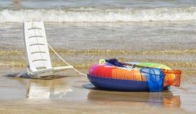Ein weißer Stuhl und ein bunter Rettungsgürtel auf der Küstenlinie Lizenzfreies Stockfoto