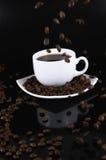 Ein weißer Tasse Kaffee mit ausfallen Kaffeebohnen Stockbild