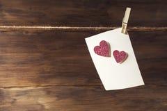 Ein weißes Blatt Papier hängend an der Wäscheklammer auf dem Blatt von empfindlichen rosa glänzenden Herzen, ein Platz zum Test Stockfoto