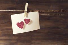 Ein weißes Blatt Papier hängend an der Wäscheklammer auf dem Blatt von empfindlichen rosa glänzenden Herzen, ein Platz zum Test Lizenzfreies Stockfoto