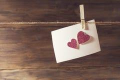 Ein weißes Blatt Papier hängend an der Wäscheklammer auf dem Blatt von empfindlichen rosa glänzenden Herzen, ein Platz zum Test Stockbild