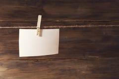 Ein weißes Blatt Papier hängend an der Wäscheklammer, Platz für Text, auf einem Hintergrund von altem hölzernem Lizenzfreies Stockfoto