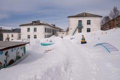 Ein weißes Gebäude des Kindergartens mit einem Kind-` s Spielplatz bedeckt mit Schnee Stockfotografie