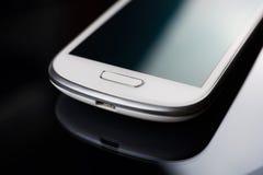 Ein weißes Geschäft Smartphone mit Reflexion auf einem leeren Tablet Lizenzfreies Stockfoto