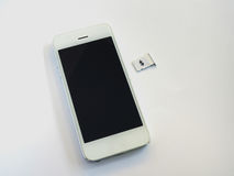 Ein weißes intelligentes Telefon, ein SIM-Karten-Behälter und ein kleines Papier wie simuliert Lizenzfreie Stockfotografie