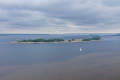 Ein weißes Segelboot mitten in dem Fluss Ein einsames Segelboot landschaften Stockbilder