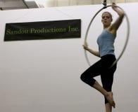 Ein weiblicher Akrobat schwingt von einem Luftband stockfotos