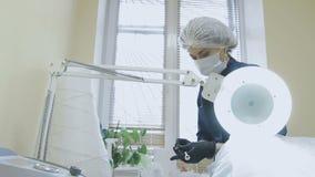 Ein weiblicher Angestellter der Cosmetologyklinik bereitet Werkzeuge für das Verfahren vor stock video footage