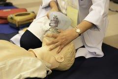 Ein weiblicher Arzt, der Gesichtsmaske auf einem Mannequin während CPR t hält stockfotos