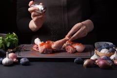 Ein weiblicher Chef besprüht frische rohe Hühnertrommelstöcke auf einem dunklen Hintergrund mit Seesalz Nahe gelegene Lüge die Be Lizenzfreies Stockbild