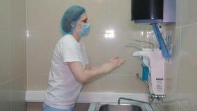 Ein weiblicher Chirurg wird zur Chirurgie fertig Er wäscht seine Hände Benutzt ein spezielles Gel für Desinfektion stock video