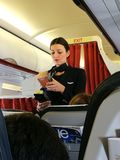 Ein weiblicher Flugbegleiter, der heraus ein Einzelteil gerade gekauft von überprüft Stockfotos