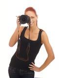 Ein weiblicher Fotograf des jungen Redhead mit einer Kamera Lizenzfreies Stockfoto