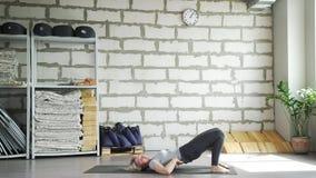 Ein weiblicher Lehrer hilft einer Frau, Übungen durchzuführen Bemannen Sie das Handeln der Hälfte, die in einer sitzenden Lotosst stock footage
