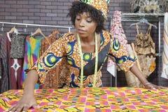 Ein weiblicher Modedesigner des Afroamerikaners, der an einem Musterstoff arbeitet Lizenzfreie Stockfotos