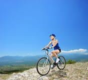 Ein weiblicher Radfahrer, der ein Gebirgsfahrrad radfährt Stockfotografie