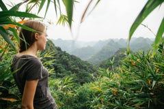 Ein weiblicher Reisender steht unter dem Dschungel und bewundert die atemberaubende Landschaft lizenzfreie stockfotos
