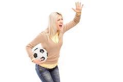 Ein weiblicher Sportfreund, der einen Fußball und ein Schreien anhält Stockfotos