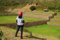 Ein weiblicher Tourist, der den eindrucksvollen Inka landwirtschaftlich und die Bewässerungsruinen von Tipon im heiligen Tal, Cus stockfotografie