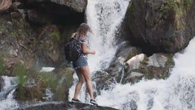 Ein weiblicher Tourist mit einem Rucksack klettert auf den Rand einer Klippe und hebt seine Hände oben vor einem großen Wasserfal stock footage