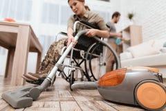 Ein weiblicher Veteran in einem Rollstuhl säubert das Haus Sie ` s in der Militäruniform Lizenzfreie Stockfotografie