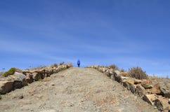 Ein weiblicher Wanderer auf einem Gebirgsweg, Spur, sonniger Tag, Titicaca See stockbild