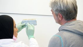 Ein weiblicher Zahnarzt im hijab einen Patienten konsultierend, den Schatten von Zähnen färben, um zu nehmen stock footage
