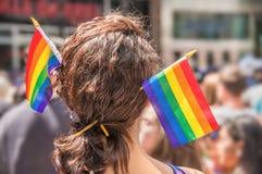 Ein weiblicher Zuschauer mit zwei Regenbogenflaggen-Haarstöcken stockfotos