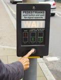 Ein weibliches Handpressen der Steuerknopf einer Pelikan-Überfahrt im Vereinigten Königreich Stockfotografie