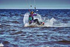 Ein weibliches kiter schiebt auf die Oberfläche des Wassers stockbild