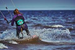 Ein weibliches kiter schiebt auf die Oberfläche des Wassers Spritzt von der Wasserfliege auseinander lizenzfreie stockbilder