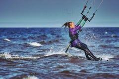 Ein weibliches kiter schiebt auf die Oberfläche des Wassers Spritzt von der Wasserfliege auseinander stockfoto