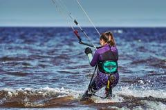 Ein weibliches kiter schiebt auf die Oberfläche des Wassers Spritzt von der Wasserfliege auseinander stockfotografie