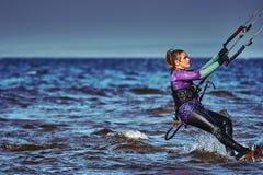 Ein weibliches kiter schiebt auf die Oberfl?che des Wassers Spritzt von der Wasserfliege auseinander lizenzfreie stockfotos
