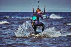 Ein weibliches kiter schiebt auf die Oberfl?che des Wassers Spritzt von der Wasserfliege auseinander stockfotografie