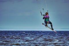 Ein weibliches kiter springt über einen großen See stockfoto
