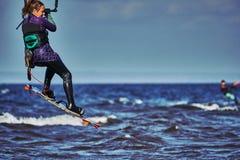 Ein weibliches kiter springt über einen großen See lizenzfreie stockfotografie