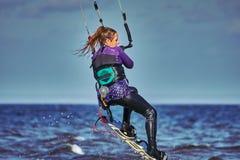 Ein weibliches kiter springt über einen großen See lizenzfreie stockbilder