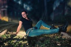 Ein weibliches Modell sitzt zwischen dem Bahngleis Lizenzfreie Stockfotografie