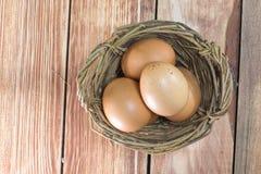 Ein Weidenkorb mit drei Eiern von der Draufsicht lizenzfreie stockbilder