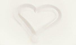 Ein weißes oder beige Herz im Sand Stockbild